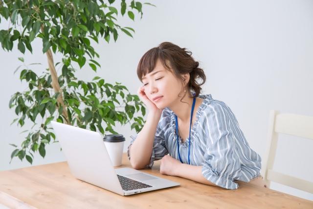 食後の眠気に襲われる女性